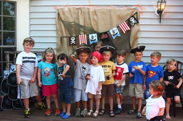 Pirate party kids with pirate hats and pirate backdrop